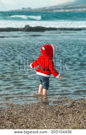 Cute baby boy in red santa coat with hood and wet shorts walks barefoot in blue sea water on pebble beach on sunny summer day on natural background