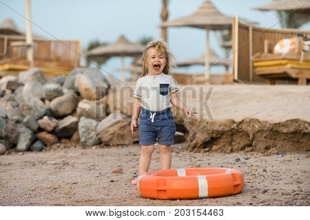 Happiness and expressive emotions. Small kid posing near orange life ring at beach. Safety on water on summer vacations. Boy child standing in life buoy. Baby care and childhood concept.