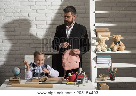 Home education and family concept. Kid and man by desk with school supplies. Girl and father in classroom on white brick background. Schoolgirl and dad with happy and strict faces hold schoolbag