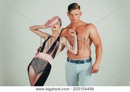 Couple in love posing on grey background. Woman or girl wearing sexy lingerie and veil hat. Fitness and beauty. Man or macho with muscular torso in black top hat. Fashion and style concept.