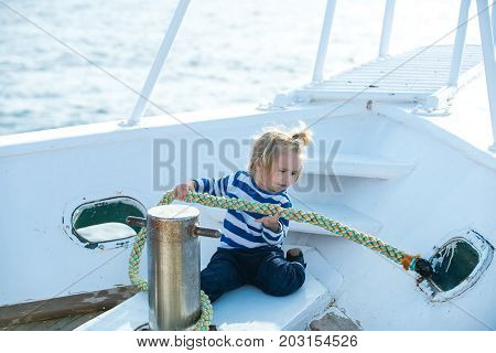 Little child sitting and berthing rope on white boat. Baby care and childhood. Travel and summer vacations. Boy kid playing with rope on yacht. Yachting and sailing concept.