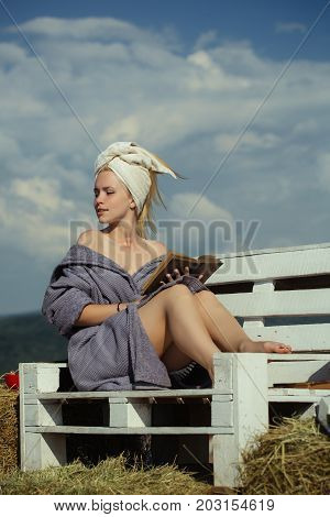 Girl in bathrobe and towel on head. Summer holidays and vacation. Student sunbathing on sunny day on natural background. Spa and wellness concept. Woman reading book on bench.