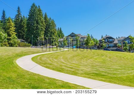 Paved pathway over green lawn on the in front of new townhouses. Park area in front of family homes on sunny day with blue sky background