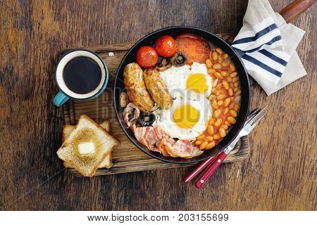 Full English breakfast with cup of coffee on wooden table top view