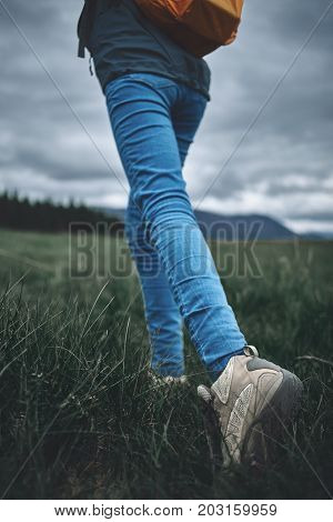 feet of woman hiker hiking in beautiful mountains on the green pines background