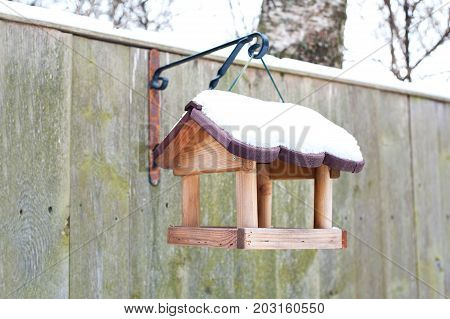Hanging bird feeder covered by snow in winter. Outdoors closeup.