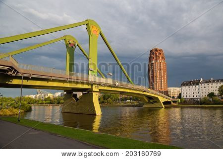 Bridge Floesser across the river Main at sunset. View from the embankment. Frankfurt am Main city. Germany