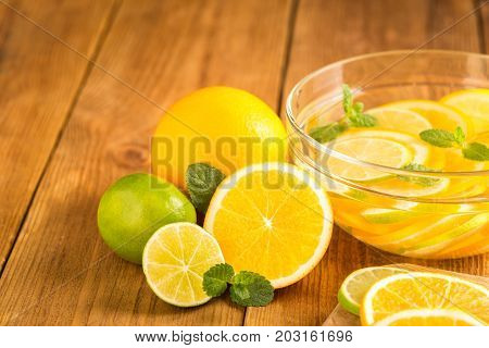 Glass Bowl With Detox Water With Slices Of Orange And Lime.
