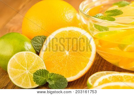 Glass Bowl With Detox Water With Slices Of Orange And Lime. Clos