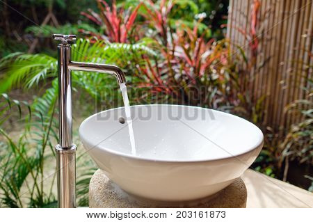 Water tap with water drop outdoor against beautiful green park background / Water saving concept