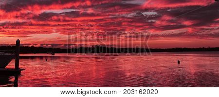 Crimson Nautical Sunset Seascape at a marina in Tin Can Bay Queensland Australia.