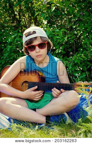 Happy ten year old boy playing guitar and singing a song in the park. Sunny summer holidays.