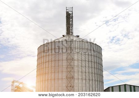 Agricultural Silo. Metal grain facility with silo. Storage and drying of grains wheat corn soy sunflower against the blue sky with white clouds