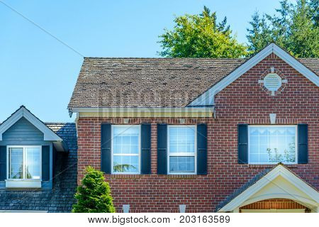 A perfect neighborhood. Houses in suburb at Summer in the north America. Top of a luxury house with nice window over blue sky.