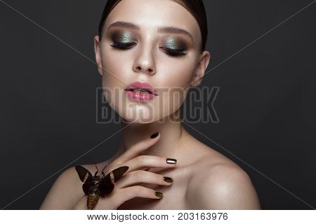 Portrait of beautiful girl with colorful make-up and cicada. Beauty face. Photo taken in the studio.