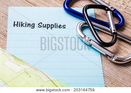 Hiking Supplies list concept on notebook and wooden board and carabiners