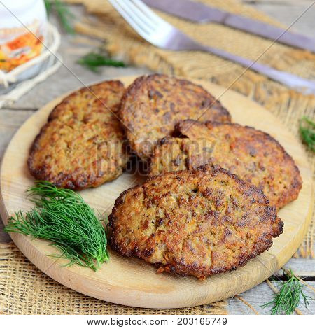 Roasted cutlets made from chicken liver mince, carrot and onion. Fast easy liver cutlets on a wooden cutting board. Closeup