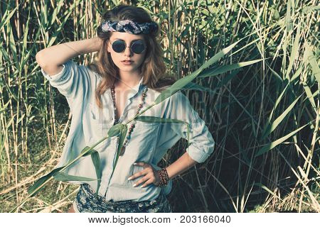 Beautiful hippie girl stands among the reeds. Spirit of freedom. Fashion shot. Bohemian, bo-ho style.