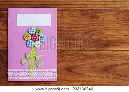 Mother's day or birthday greeting card with flower isolated on a wooden background with copy space for text. Simple handmade card to make in school or at home. Paper crafts for kids. Closeup. Top view