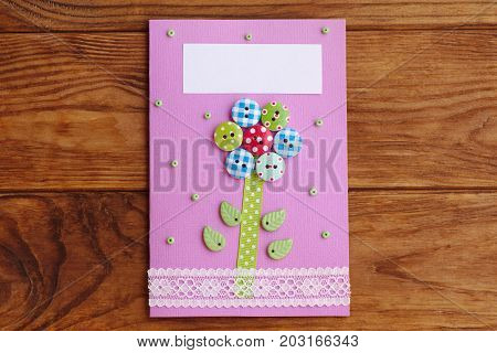 Mother's day or Mom birthday greeting card with flower isolated on a wooden background. Easy handmade card to make in school or at home. Simple craft work with paper for kids. Closeup. Top view