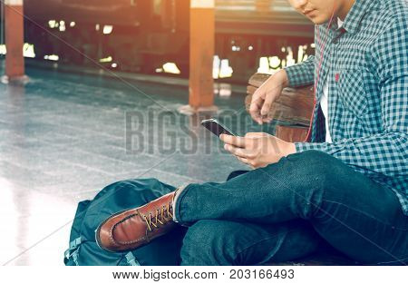 Asian Hipster Smart Man Holding Mobile Phone Using App Song With Linten Music At Train Station.
