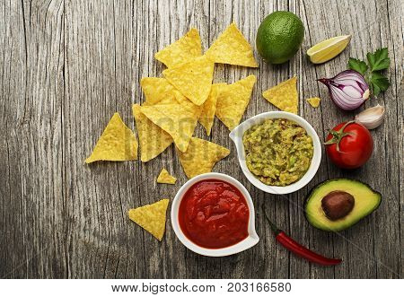 Avocado guacamole and tomato salsa with fresh ingredients on table