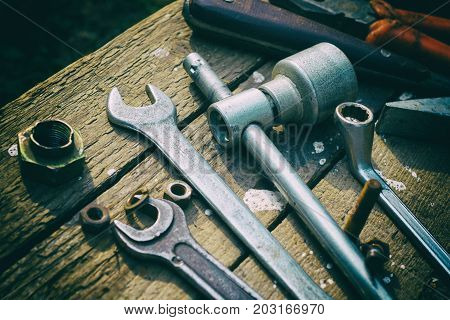 On weathered old wooden surface lie the old, oily wrenches, pliers, screwdrivers and metal brush. Near scattered old rusty nuts. Imitation of shooting on a film.