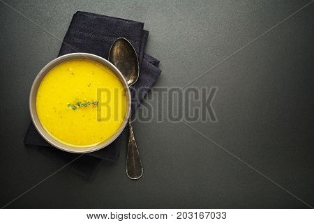 Healthy vegetable cream soup with herbs on dark background Top view