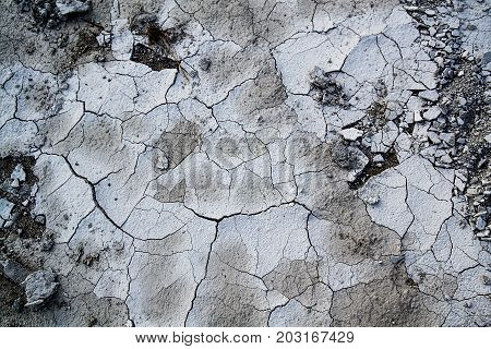 Cracked concrete texture background. Grey surface with cracks close up.