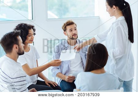 New activity. Professional friendly group therapist holding sheets of paper and giving them to her patients while preparing to start doing a new psychological activity