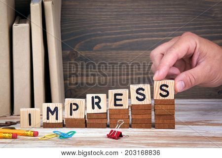Impress concept. Wooden letters on the office desk, informative and communication background.