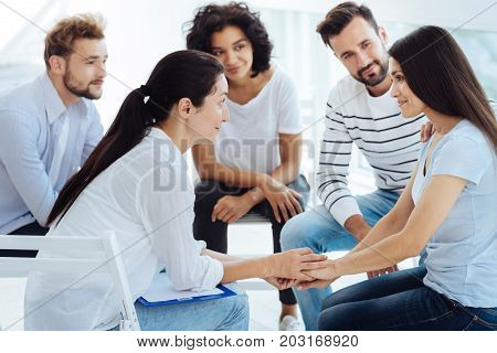 I am so grateful. Positive delighted young woman holding her therapists hands and smiling while being thankful for support