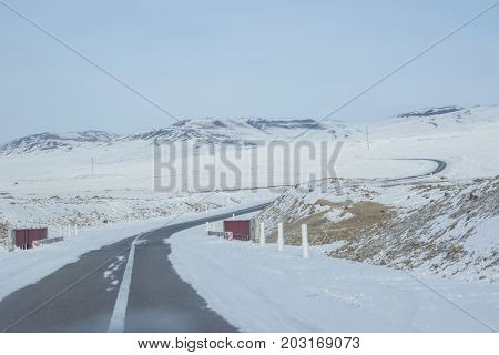 Landscape of empty highway bend surrounding by snow under blue sky in winter season its make feeling solitary, Slippery frozen long asphalt road on nature with frost covered ground and mountain range in Bled at Slovenia, Perspective of S-shape rural road