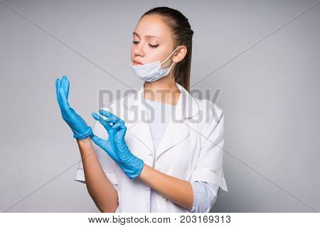 the nurse takes off the blue glove.on a gray background