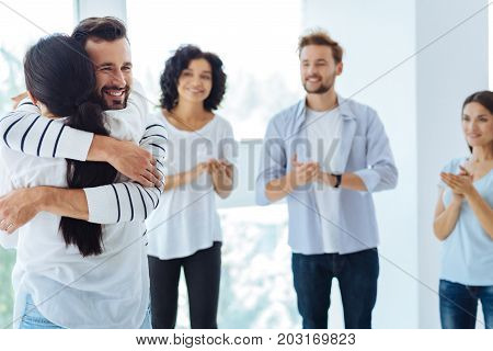We are friends. Delighted cheerful handsome man hugging a woman and smiling while being in a great mood