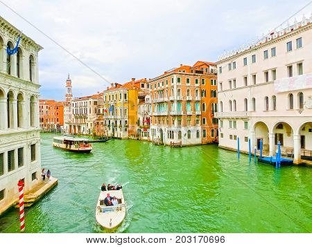 Venice, Italy - May 04, 2017: The boats and gondola sails down the channel in Venice, Italy on May 04, 2017. Gondola is a traditional transport in Venice, Italy