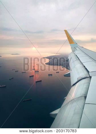 View from the window of a flying aircraft on the seashore and trawler boats on the seawater