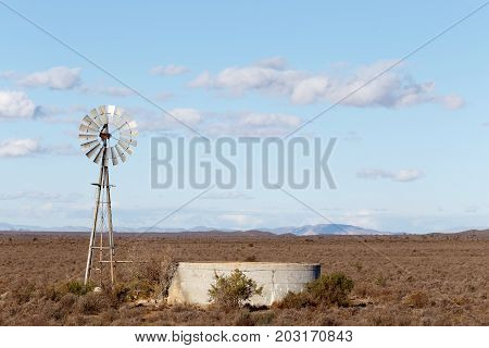 Windmill With A Dam In The Field