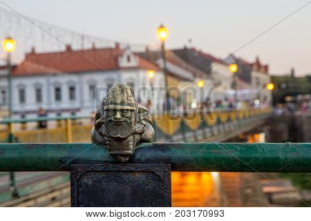 Uzhgorod Ukraine August 29 2017: Mini sculpture of Mikolajczyk the Santa's helper on the handrail of the bridge on the background of the evening city