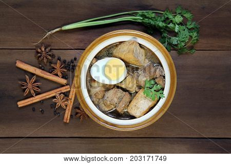 Belly Pork Chinese Five-Spice Stew with boiled egg and fried tofu braised in brown sauce decorated with anise star black pepper cinnamon and coriander on wooden background, Asia food.