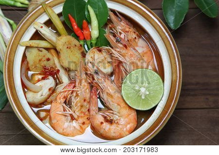 Tom Yum Goong clear soup on wooden background, hot and sour Thai soup, food.