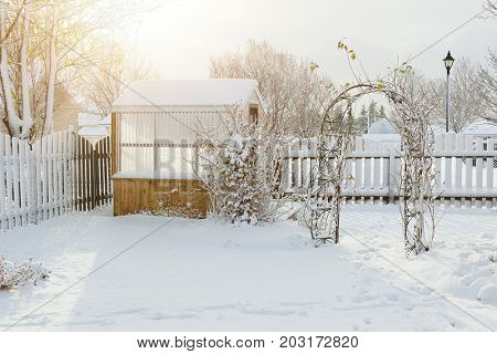 Greenhouse and arbor covered in snow in an urban back yard.