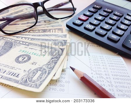 Business, finance, saving money, banking, loan, investment, currency exchange, taxes or accounting concept : Dollar money, calculator and saving account book or financial statement on office table