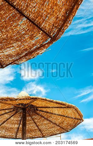 Wattled straw beach umbrella on blue cloudy sky background. Outdoors summertime multi colored closeup vertical image. View from below.