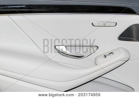 Door handle with Power seat and window contol buttons of a luxury passenger car. White leather interior of the luxury modern car. Modern car interior details