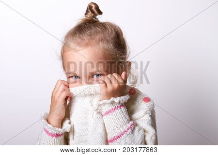 Portrait of a charming little girl in beige sweate. hides his nose. child playing peekaboo.  hiding inside the neck of her pullover while smiling at the camera