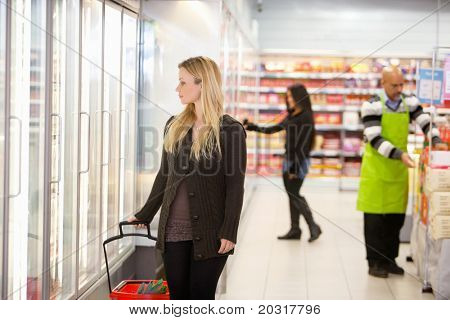 Woman in shopping mall looking through cooler window with people in the background
