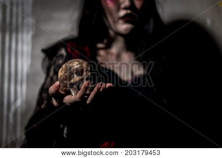Witch death the ghost holding skull and zombie in dress women with blood skin is screaming darkness and nightmare background horror of scary fear on hell is monster devil girl in halloween festival