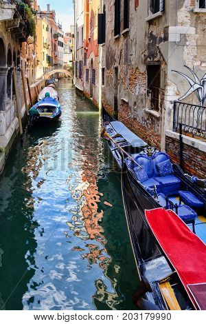 Gondolas and small boats on a narrow canal in Venice surrounded by old buildings