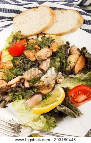 mussel salad with tomato lemon and bread on a plate